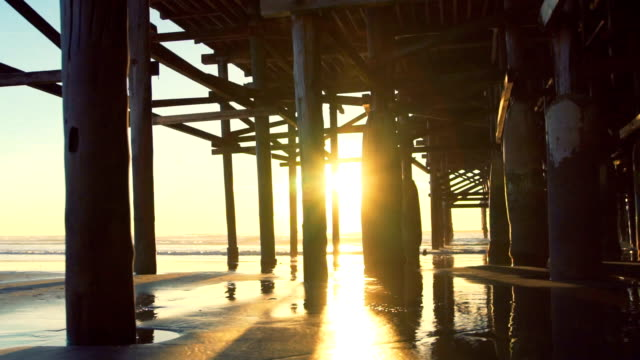 Amazing Sunset Light Flares Under Pier. Beach Sunset. 4K video