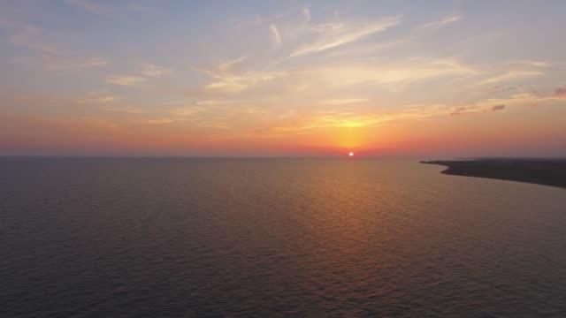 vídeos de stock, filmes e b-roll de antena: incríveis pôr do sol sobre o mar calmo - multicóptero