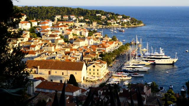 fantastisk solnedgång över hvar stad och bay med yachter, ön hvar, kroatien - stenhus bildbanksvideor och videomaterial från bakom kulisserna