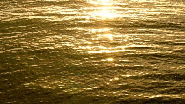 stockvideo's en b-roll-footage met 4k verbazingwekkend zonsondergang over het tropische strand. oceaan strand golven op het strand bij zonsondergang, zonlicht overdenkt wateroppervlak. mooie avond natuur zee achtergrond. - baai