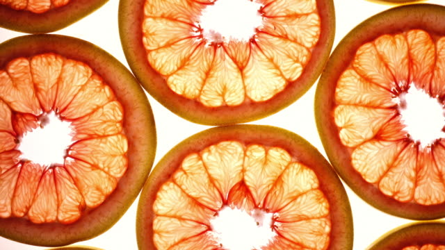 Amazing top view of grape-fruit slices in flat lay close up, rotating contra clockwise.