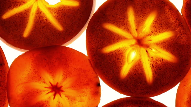 vídeos de stock e filmes b-roll de amazing top view of persimmon fruit slices in flat lay close up, rotating clockwise with down center. - diospiro