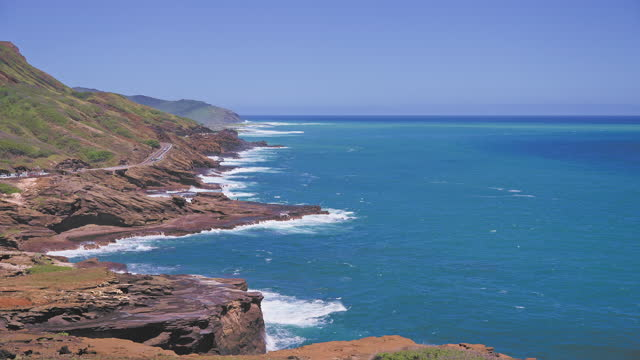 Amazing view of the rocky coast of Oahu Hawaii. The turquoise waves of the Pacific Ocean wash over volcanic rocks. Summer vacations in Hawaii. Lanai Lookout.