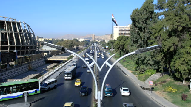 Amazing view over circulation in Damascus, Syria. A busy highway in the capital, with the national flag in the background. View over the circulation in Damas, a lot of cars and trucks on the road. A living city even after the war. Buildings and trees in the background. War years in Syria. damascus stock videos & royalty-free footage
