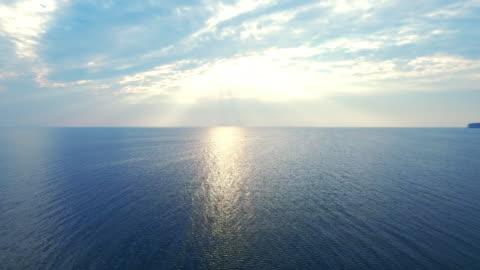 vídeos de stock e filmes b-roll de amazing view sunlight reflecting on sea surface. drone view blue sea on skyline - mar