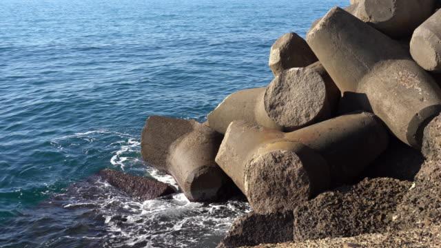 海水の洪水を防ぐためのビーチでの大規模な防衛工事、海岸に対して飛び散る驚くべき水。三角形の強力な石ブロックを持つ海桟橋の要塞 - デイフェンス点の映像素材/bロール