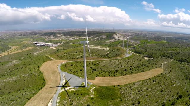 Amazing wind farm generating energy on beautiful green field, future technology video