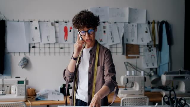 vídeos de stock, filmes e b-roll de desenhador de moda ambicioso que fala no telefone móvel em papéis da terra arrendada da oficina - designer profissional