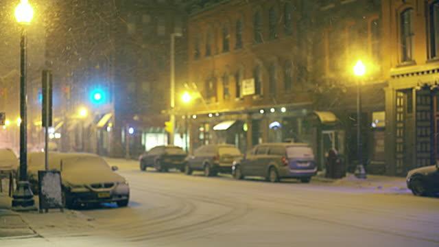 Ambulance driving on the street under snowfall