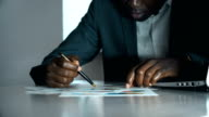 istock American african business man working on business charts in his office 1189543135