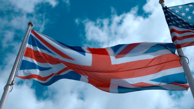 American and English flags on the flagpole waving in the wind against a blue sky video
