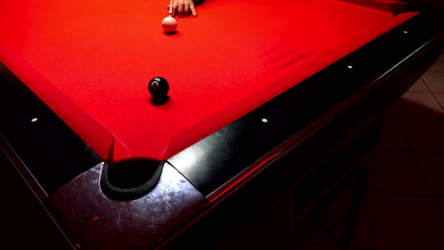 American billiard, 9-ball, nine-ball pool. Man playing billiard, snooker. Player preparing to shoot, hitting the cue ball.Ball goes through the hole. UHD Sony 4K shoot video