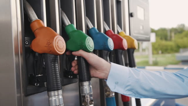 American businessman taking fuel nozzle in hand for refilling car at gas station