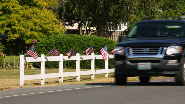 American car truck suv passing patriotic display of American flags waving on white picket fence. Fourth of July 4th Independence Day decorations HD video.