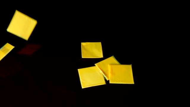 american cheese slices falling with a black background in slow motion This slow motion video shows individually wrapped american cheese slices falling with a black background. cheese stock videos & royalty-free footage