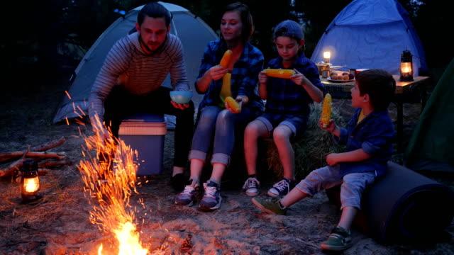 アメリカの家族は、塩、旅行、キャンプの森でのピクニックとトウモロコシを食べる、ママ、パパと息子が新鮮な黄色のトウモロコシを食べる - 息子点の映像素材/bロール