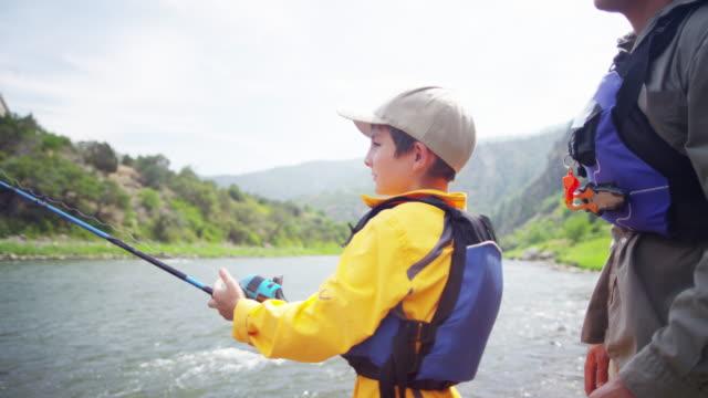 american father and son fishing together colorado river - łowić ryby filmów i materiałów b-roll