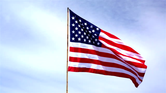 American Flag Against Blue Sky Waving Proudly In The Wind Stars And