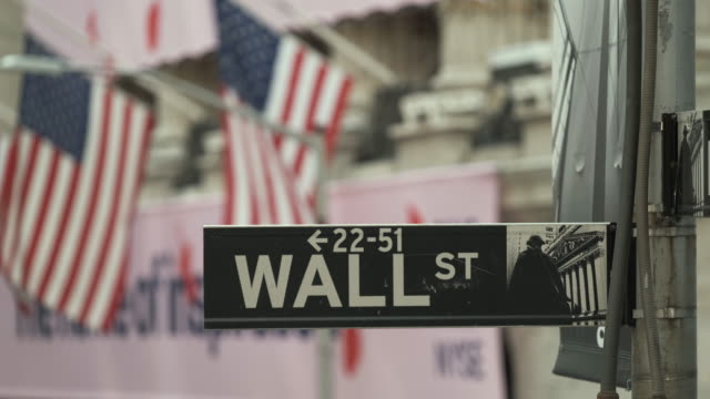 American Flag. Building Of New York. Wall Street Sign. Perspective Of American Flag Against Backdrop Of New York Skyscrapers. wall street stock videos & royalty-free footage