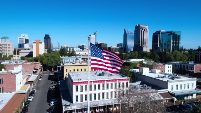American Flag flying in front of Old Sacramento and remote Sacramento Downtown. Aerial drone low-altitude video with orbit camera motion.