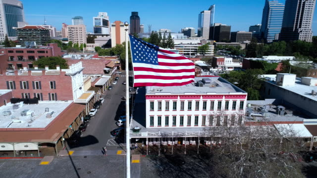 american flag flying in front of old sacramento and remote sacramento downtown. aerial drone low-altitude video with the orbit camera motion. - bandiera nazionale video stock e b–roll