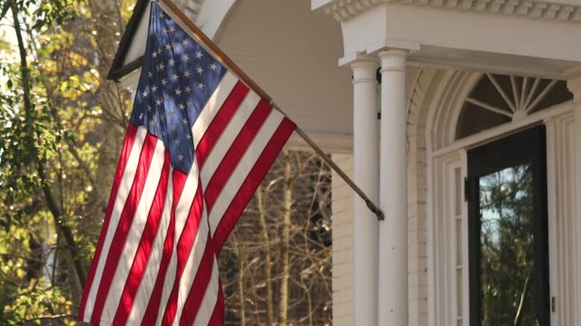 american flag hangs from a porch on charleston south carolina - giorno dell'indipendenza video stock e b–roll