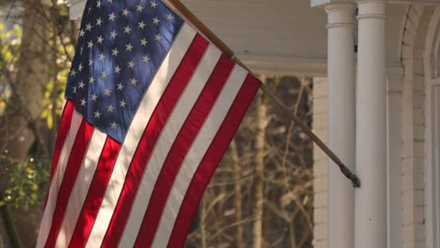 American flag hangs from a porch on Charleston South Carolina USA flag hangs from a front porch in the summer at a patriotic home in the USA porch stock videos & royalty-free footage
