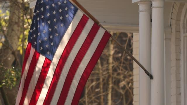 la bandiera americana pende da un portico sulla carolina del sud di charleston - portico video stock e b–roll