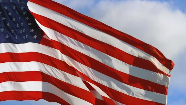 American flag is flying in the wind on a sunny day video