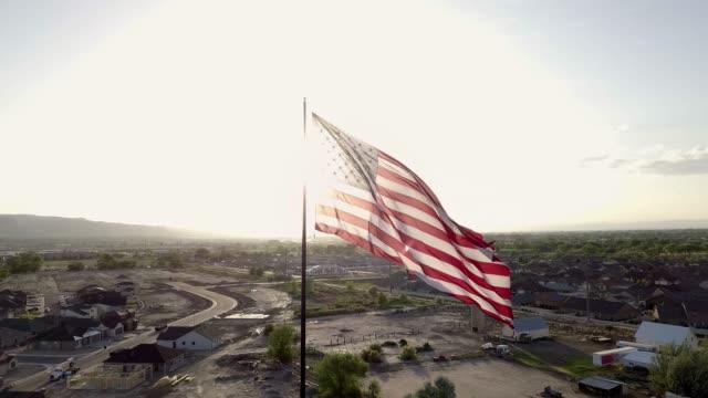 vidéos et rushes de drapeau américain sur le nouveau quartier au crépuscule - patriotisme