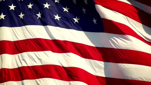 American Flag Slow Motion US Flag unfurling in the breeze Shoot with a high-speed camera. fourth of july videos stock videos & royalty-free footage