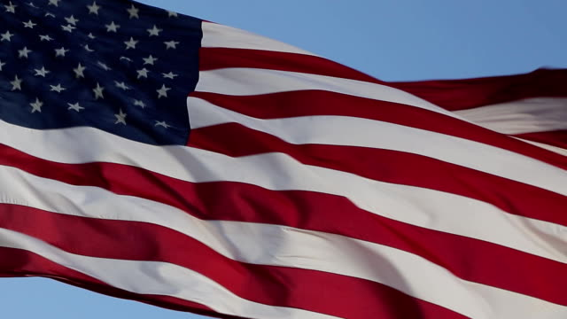 USA American Flag Waving United states of America famous flag in front of blue sky. American flag is flying in the wind on a sunny day. Symbol of the Amenrican national holiday. Independence Day - American concept. memorial day stock videos & royalty-free footage