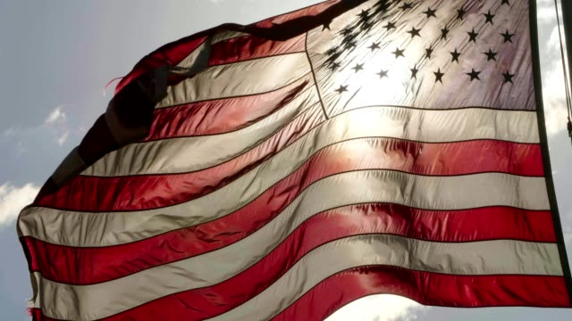 American Flag Closeup of American flag on flag pole waving in the wind. back lit stock videos & royalty-free footage
