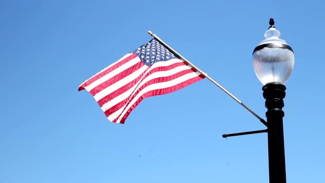 american flag waving against clear blue on black lamppost - columbus day filmów i materiałów b-roll