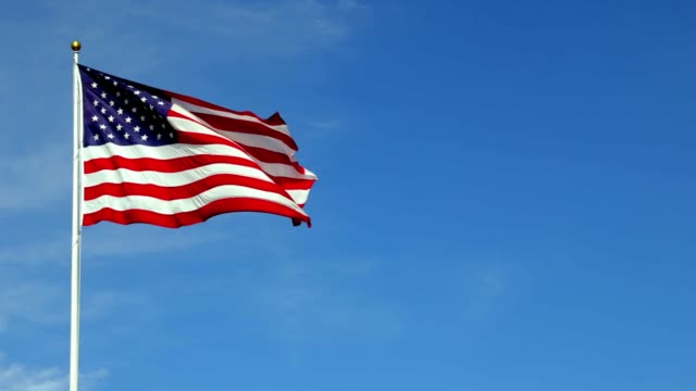American flag waving in the wind in slow motion, with vibrant red white and blue colors against blue sky, with copy space.