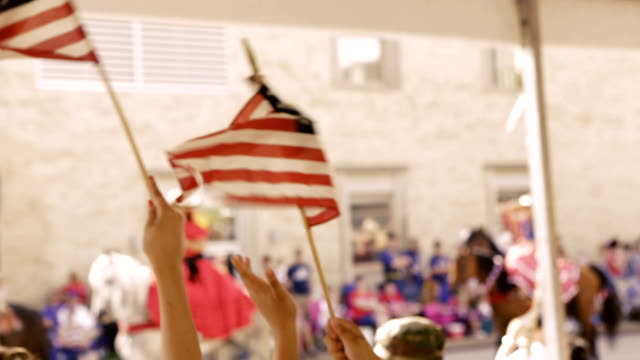 bandiere americane essere ha salutato da una famiglia che frequentano independence day parade - 4 luglio video stock e b–roll