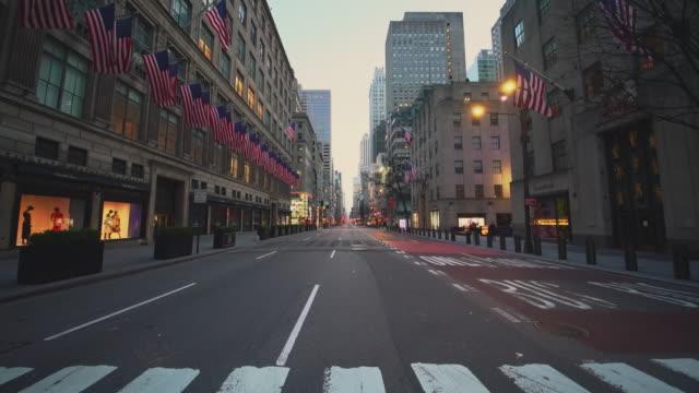 covid-19 전염병 발병으로 인해 버려진 뉴욕시에서 가장 붐비는 목적지 중 하나 인 5 번가의 미국 국기. - unemployment 스톡 비디오 및 b-롤 화면
