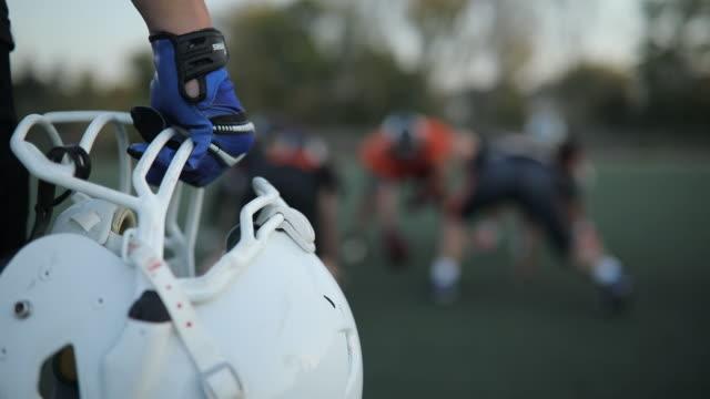 vídeos y material grabado en eventos de stock de casco de fútbol americano en un mans mano - american football