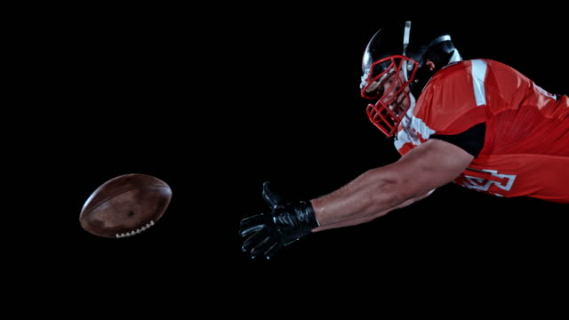 slo mo ld american football player catching the ball while airborne - guanto indumento sportivo protettivo video stock e b–roll