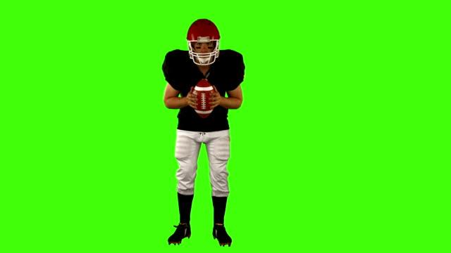 futbol amerykański gracz trzymając piłkę - trykot filmów i materiałów b-roll