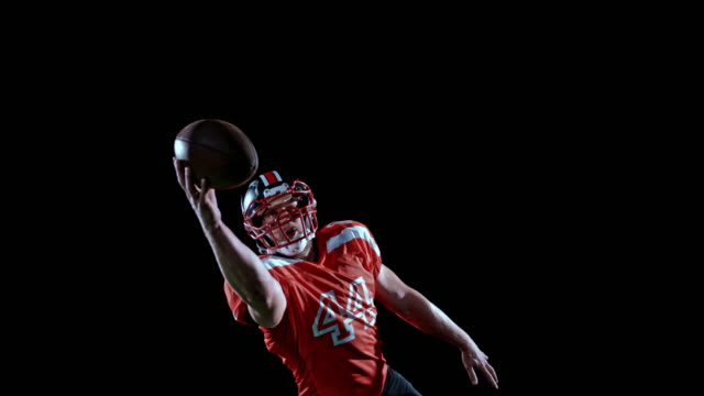 SPEED RAMP American football player in red jersey catching the ball with one hand on black background Speed ramp wide shot of an American football player in red jersey jumping into the air and catching the ball with one hand. Shot on black background. Shot in Slovenia. catching stock videos & royalty-free footage