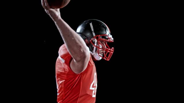 Jugador de fútbol americano de la rampa de velocidad en jersey rojo lanzando la bola sobre fondo negro - vídeo