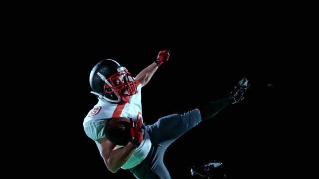 SLO MO American football player in white jersey catching the ball in the air with one hand on black background