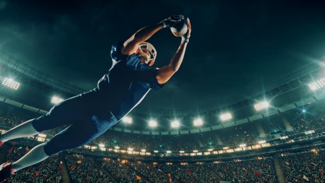 vídeos de stock e filmes b-roll de american football player jumps with a ball - desportista