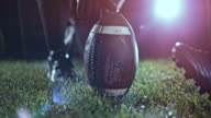istock SLO MO American football player kicking the ball held by his teammate on the field at night 700660470