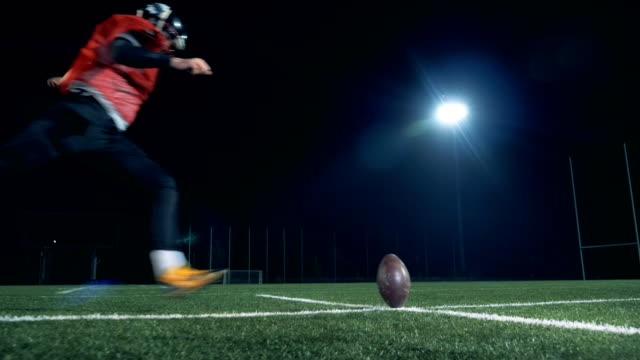 vídeos de stock e filmes b-roll de american football player scoring a goal, back view. - chutar