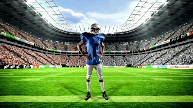 football americano triumphing con le braccia sollevate - mani sui fianchi video stock e b–roll
