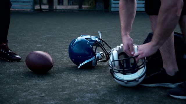 vidéos et rushes de joueurs de football américain prépare des casques - ligue sportive