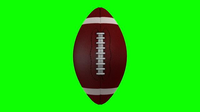 american football rotating over a chroma key background - football filmów i materiałów b-roll