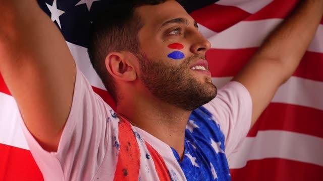 amerikanische kerl feiert mit nationalflagge - sportchampion stock-videos und b-roll-filmmaterial